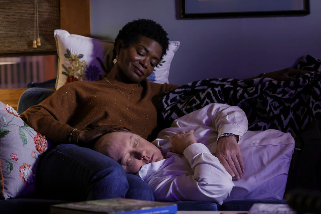 LaChanze as Anne looks down on James Spader as Raymond 'Red' Reddington as he lies his head in her lap, fast asleep. She's smiling.