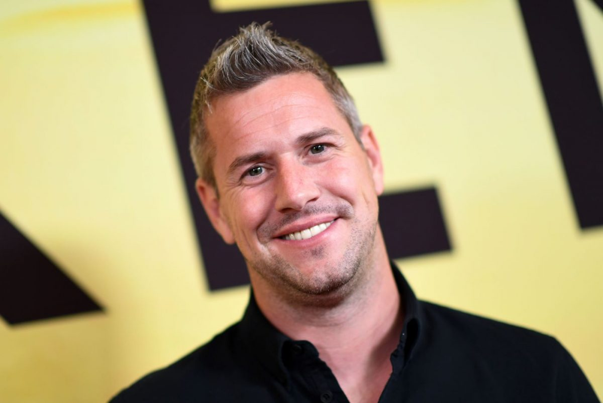 Ant Anstead wearing a black collared shirt in front of a yellow background with a black letter.