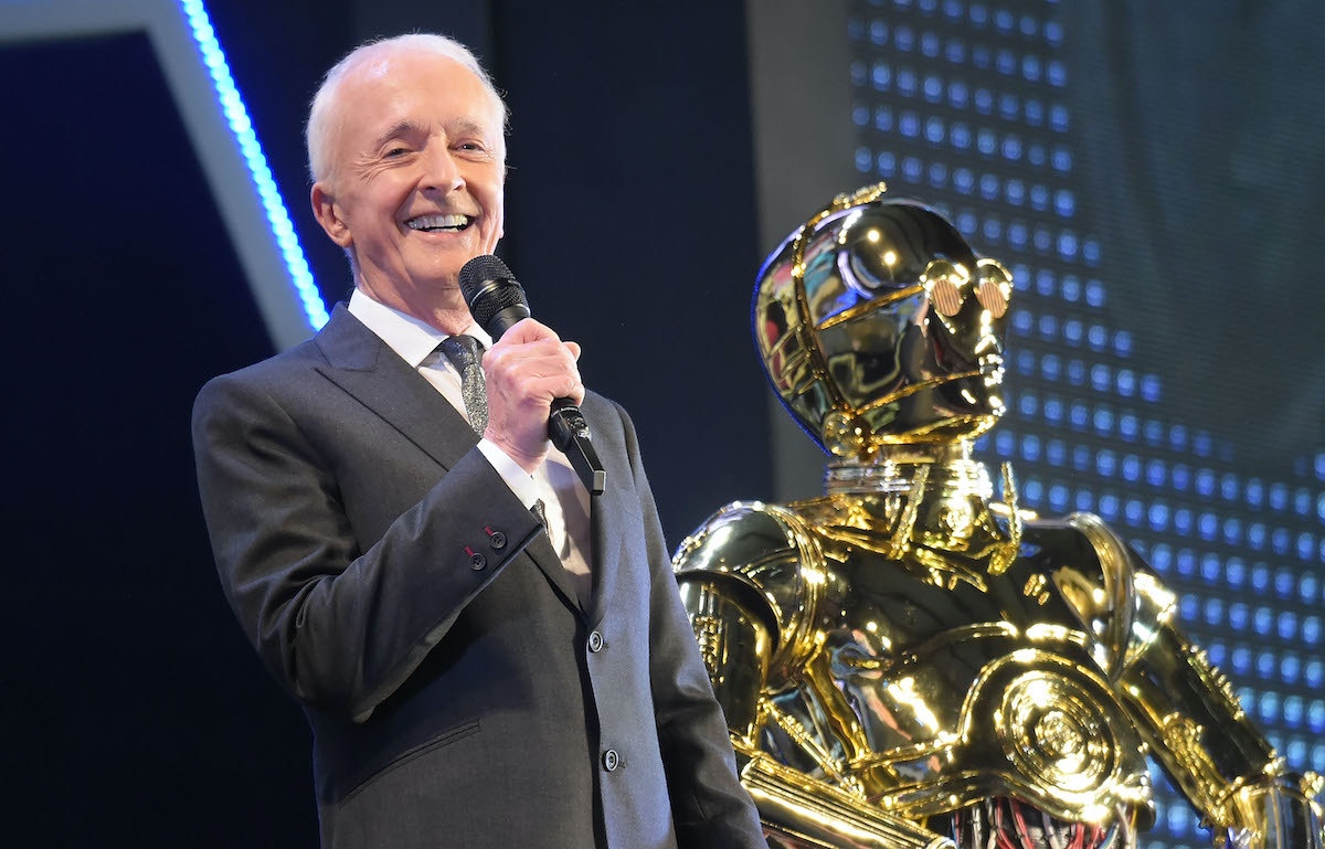 Anthony Daniels holds a microphone on stage next to C-3PO