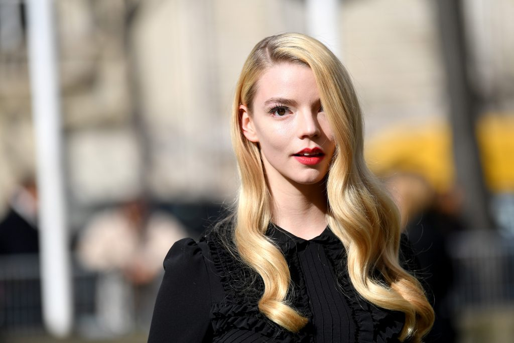 Anya Taylor-Joy in a black shirt with long blonde hair covering one eye.