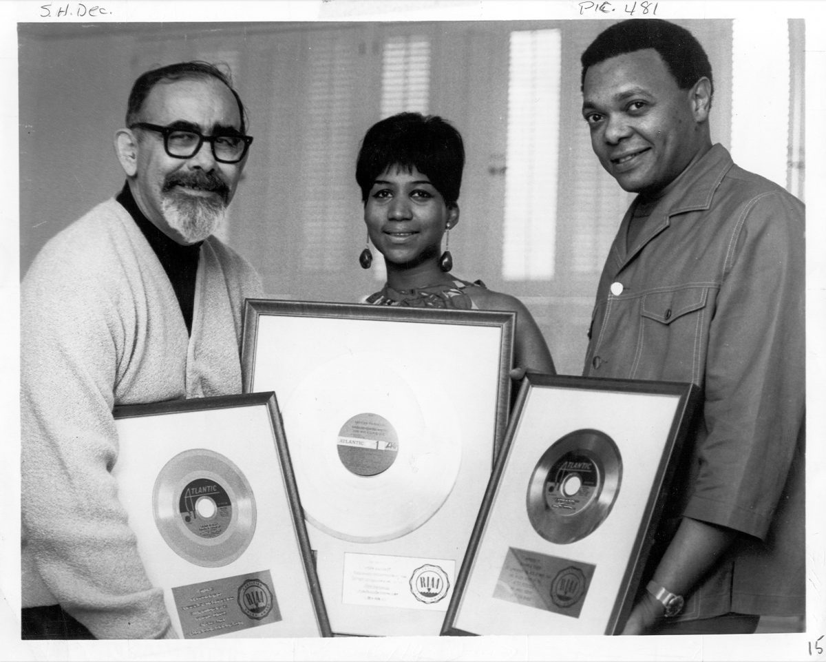 Aretha Franklin and Ted White holding framed records with producer Jerry Wexler in 1968