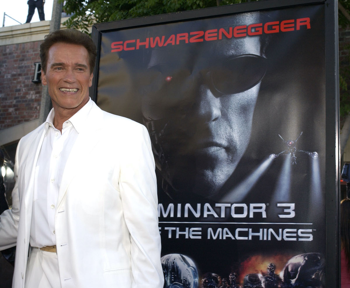 Arnold Schwarzenegger wears a white suit and poses beside artwork for 'Terminator 3: Rise of the Machines'