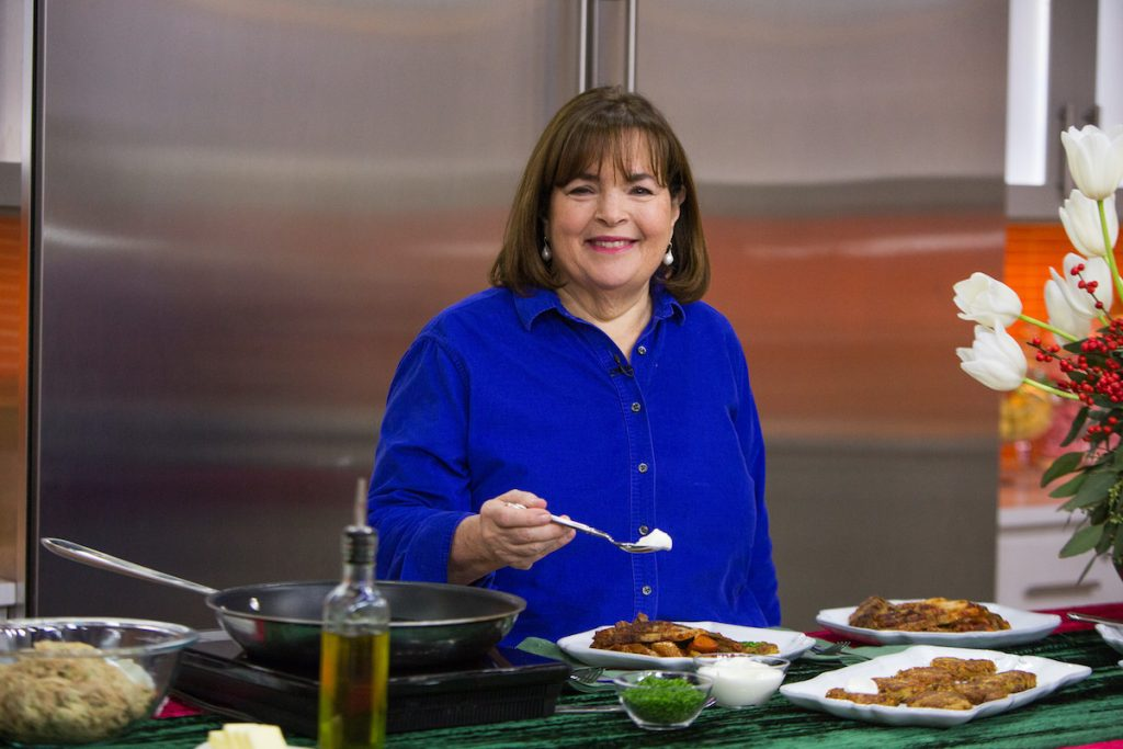 Ina Garten holds a spoon while standing behind the counter of a test kitchen