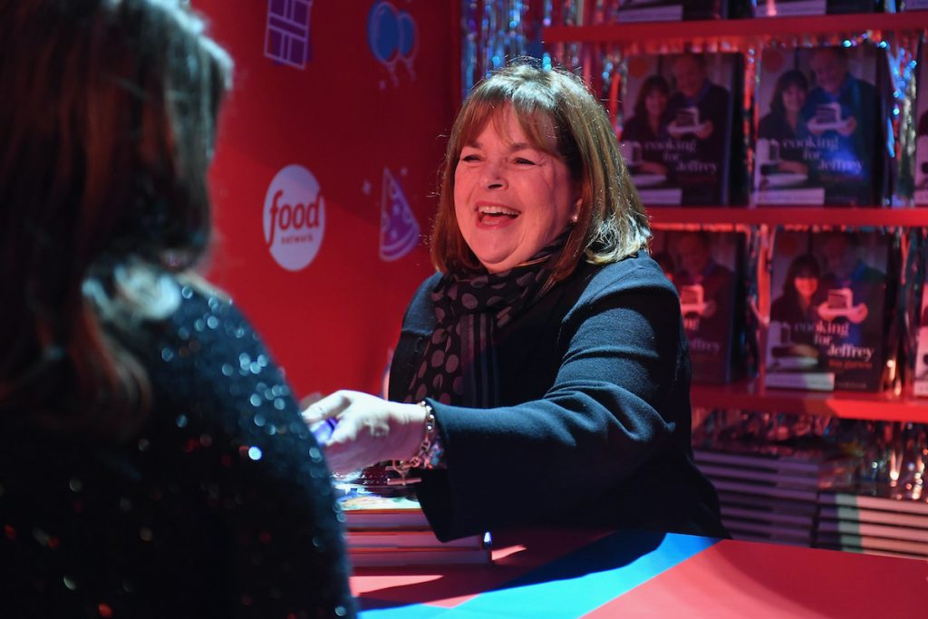 Ina Garten laughs while signing a cookbook for a fan