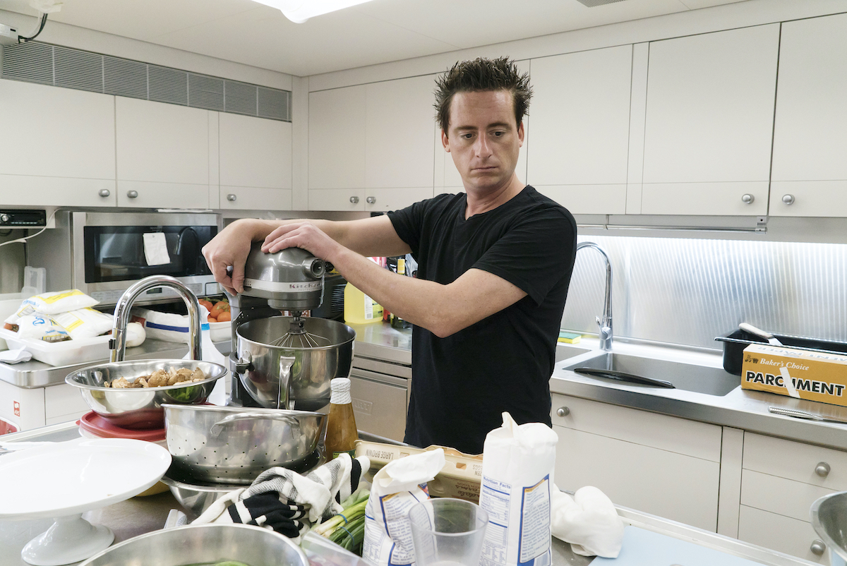 Chef Ben Robinson from Below Deck whips up dinner for the guests in the galley kitchen