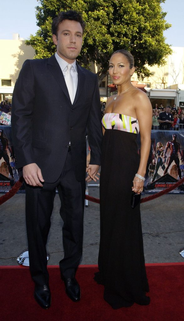 Ben Affleck and Jennifer Lopez dressed formally pose for the camera at an event.