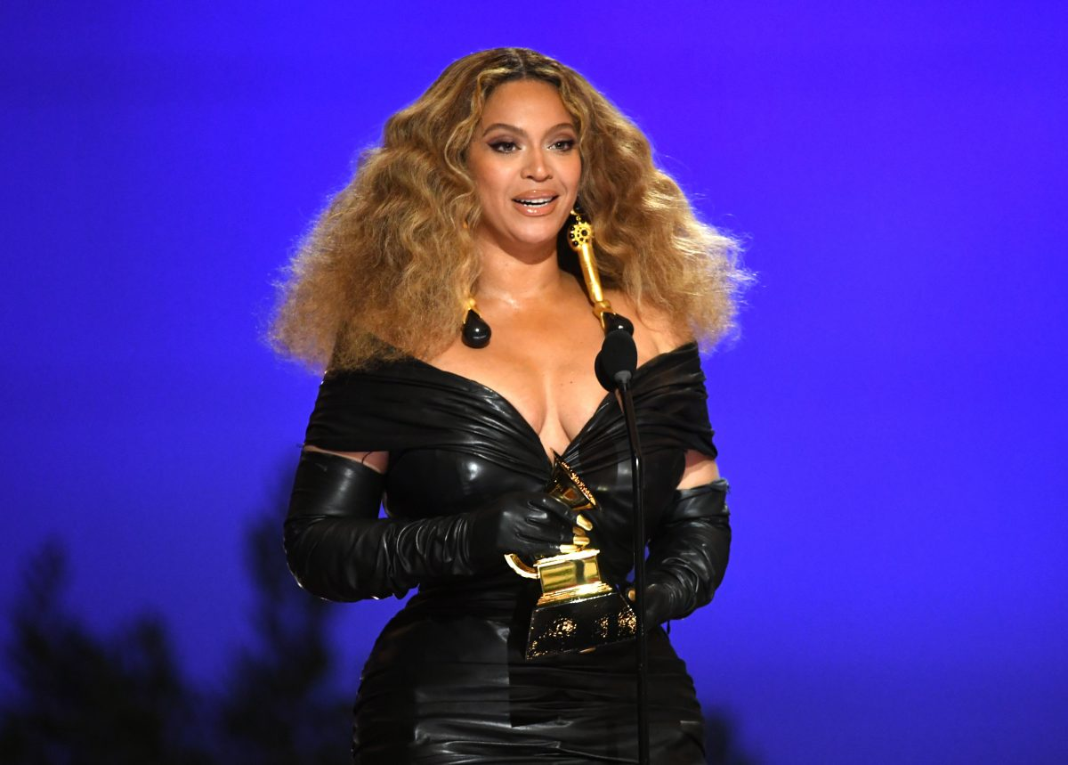 Beyoncé holding a Grammy Award in a black dress at the 2021 event.