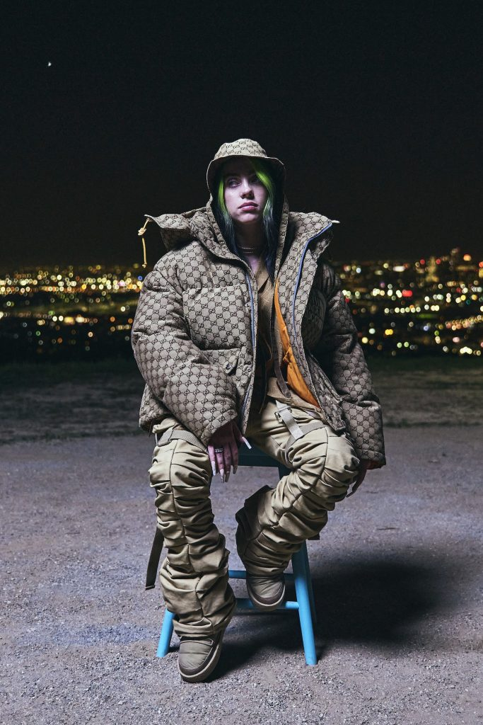 Billie Eilish alone in a chair facing the camera unsmiling, wearing an oversized puffy coat and baggy pants.