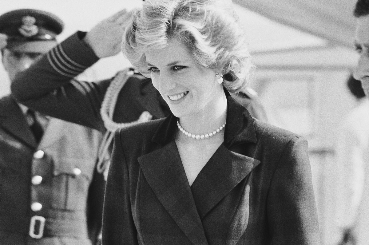 Black-and-white photo of Princess Diana in 1985 wearing an outfit designed by Catherine Walker, with pearl earrings and a pearl necklace