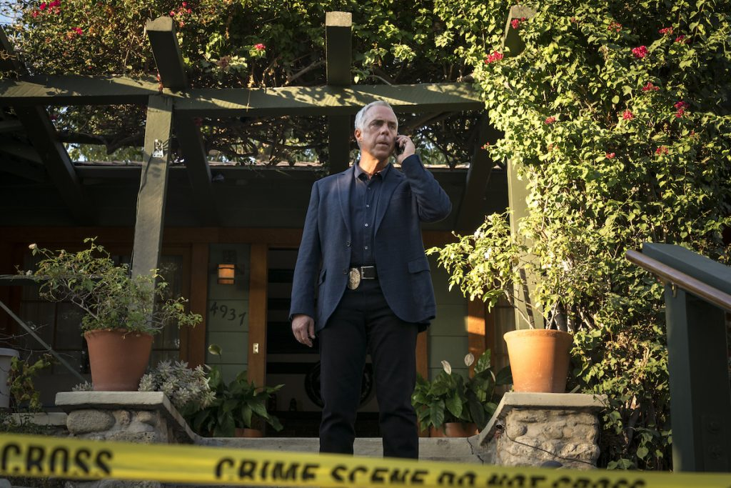 Titus Welliver as Detective Harry Bosch takes a call as he stands outside a crime scene. He's dressed in a navy suit and is surrounded by shrubs.