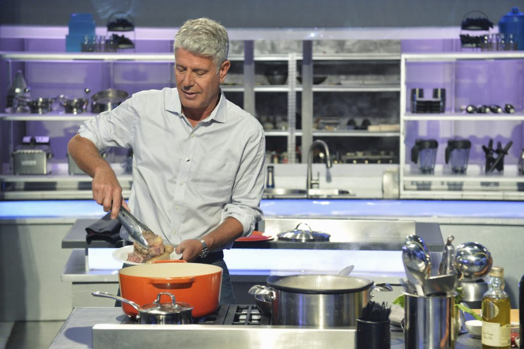 Anthony Bourdain cooking in a kitchen