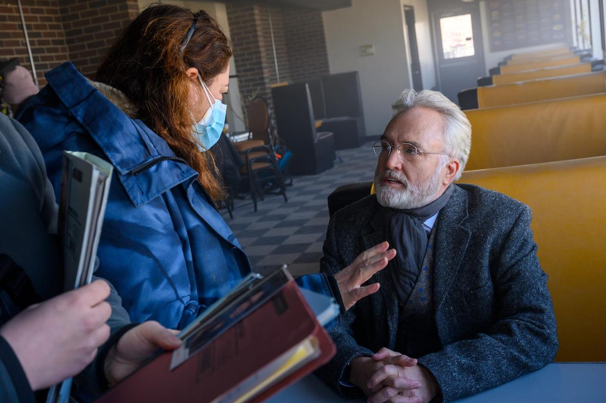 Director Liz Garbus and Commander Lawrence actor Bradley Whitford on set of 'The Handmaid's Tale' Season 4 Episode 10, 'The Wilderness.' Whitford sits in a wool coat, paisley suit vest, neck scarf, and glasses in a yellow booth at a diner in daytime. Whitford is playing Commander Joseph Lawrence in this scene and is being directed by Garbus. The floor is black and white and checkered and the walls are brick.