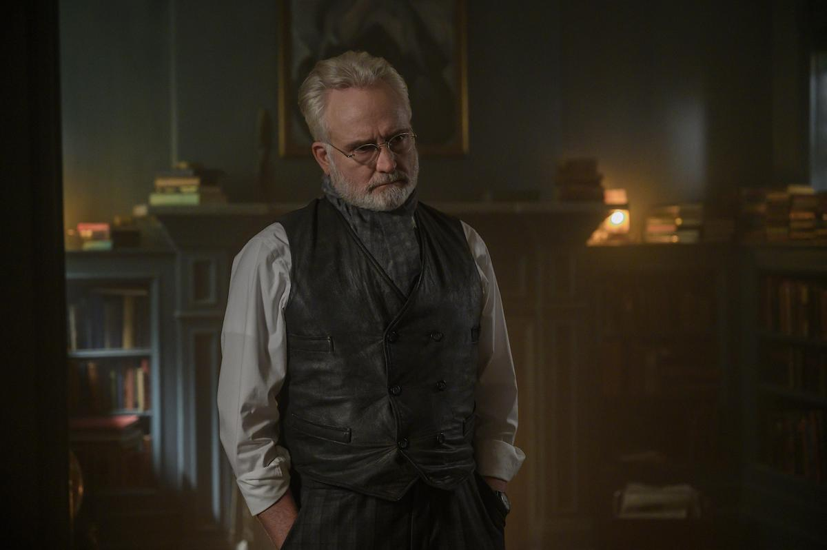 Bradley Whitford as Commander Joseph Lawrence in 'The Handmaid's Tale' Season 4 Episode 8, 'Testimony.' Bradley Whitford's character in 'The Handmaid's Tale' wasn't in Margaret Atwood's original novel, which Whitford said makes him feel 'insecure' at times. But the character is still captivating. In this photo, he stands in home library with his hands in his pockets. He wears a leather suit vest with a button-down shirt underneath and neck scarf and glasses.