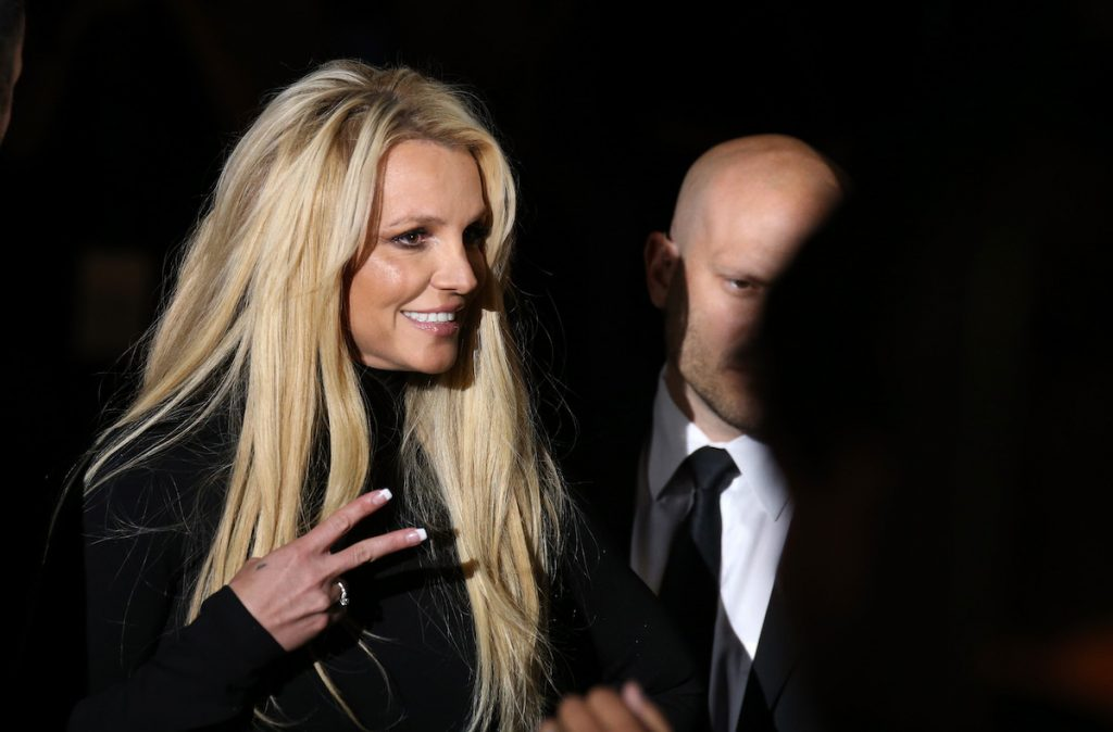 Britney Spears in black dress flashing peace sign
