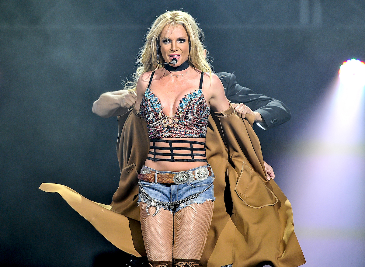 Britney Spears wearing trench coat onstage