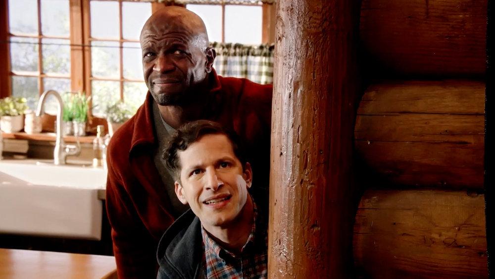 Terry Jeffords and Jake Peralta cringe while hiding behind a wall in 'Brooklyn Nine-Nine'