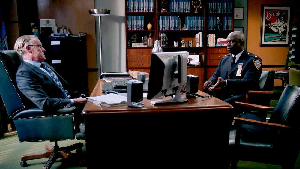 Frank O'Sullivan and Captain Ray Holt sit at a desk in season 8 of 'Brooklyn Nine-Nine'