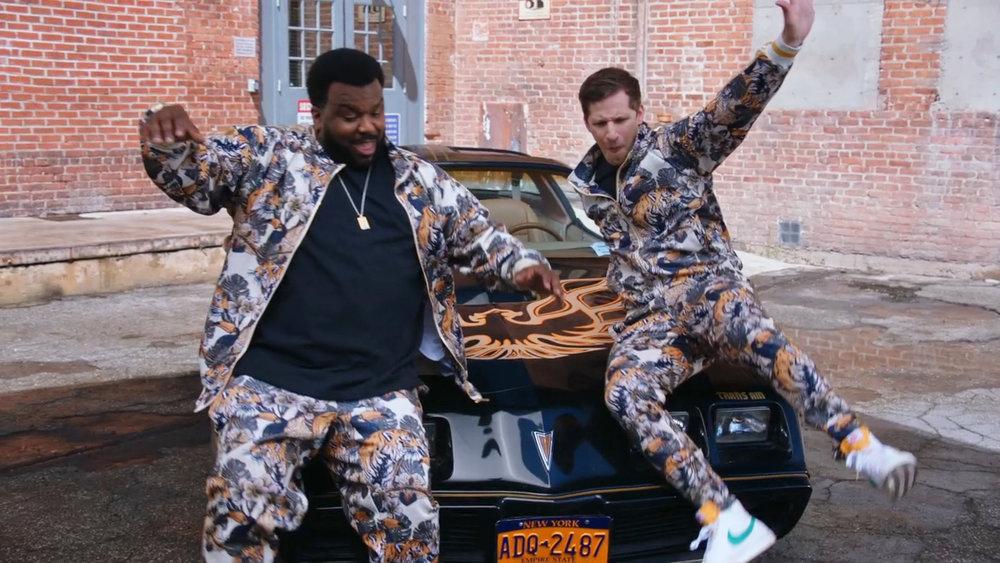 Doug Judy and Jake Peralta slide down the hood of a car in 'Brooklyn Nine-Nine'