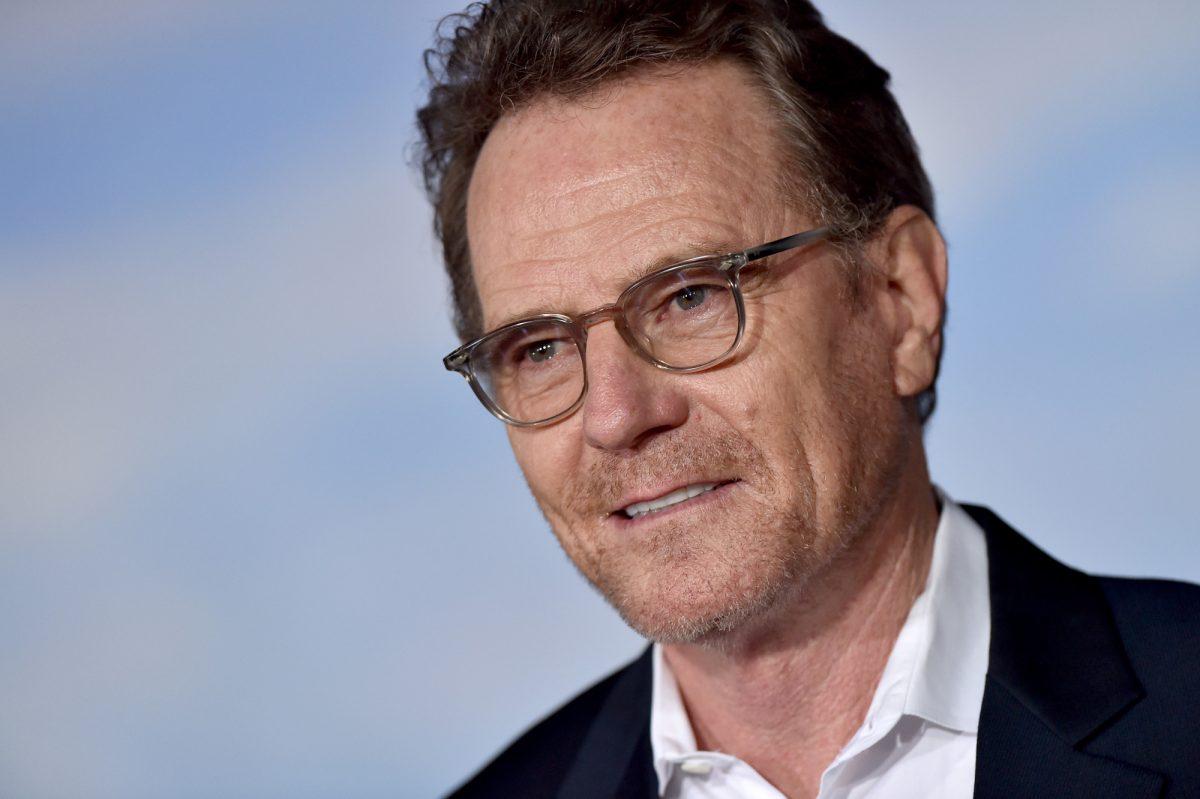 Breaking Bad's Walter White star Bryan Cranston wearing glasses and staring ahead with a blue background behind him