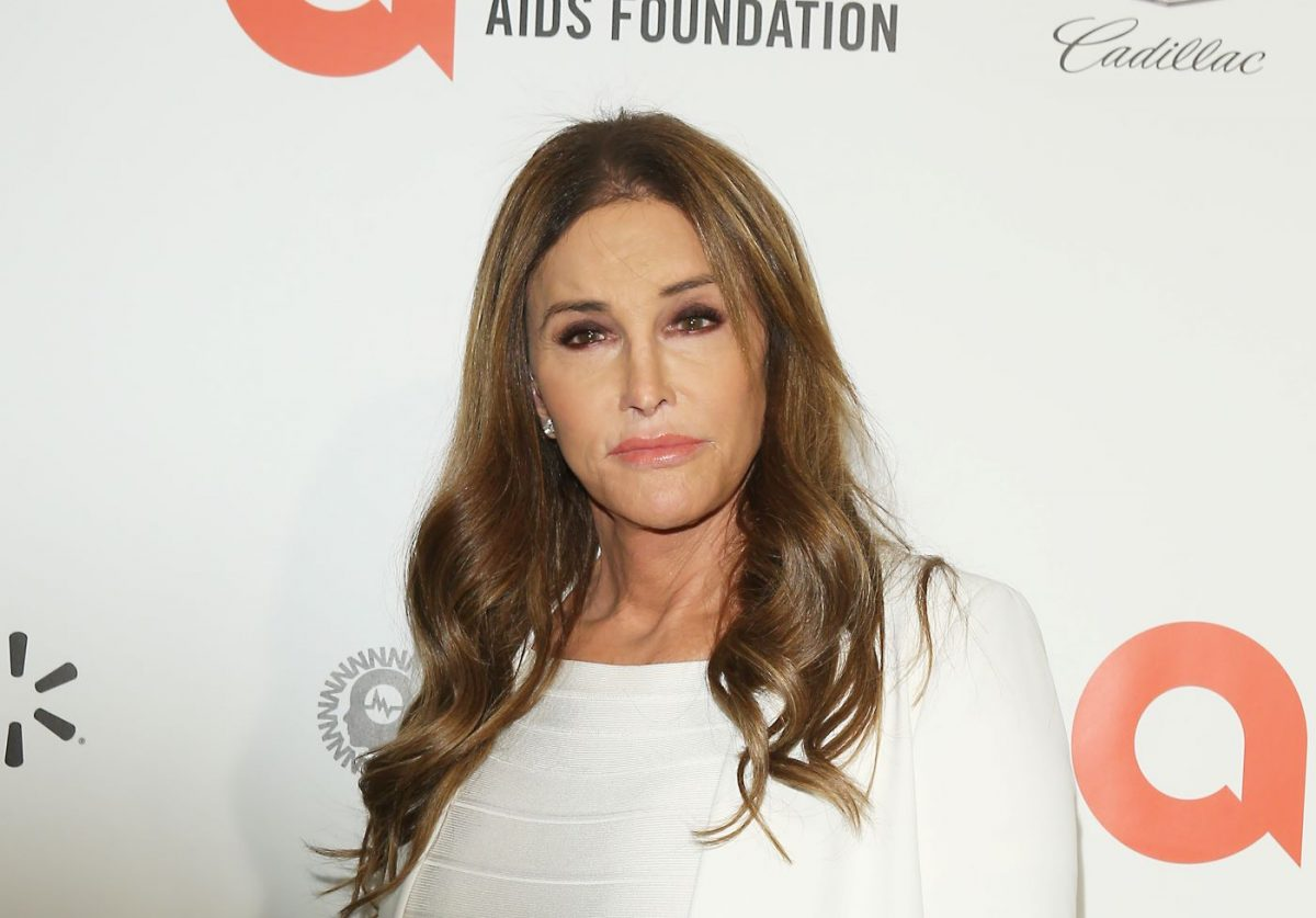 Caitlyn Jenner standing in front of a white background wearing a white top and white jacket.