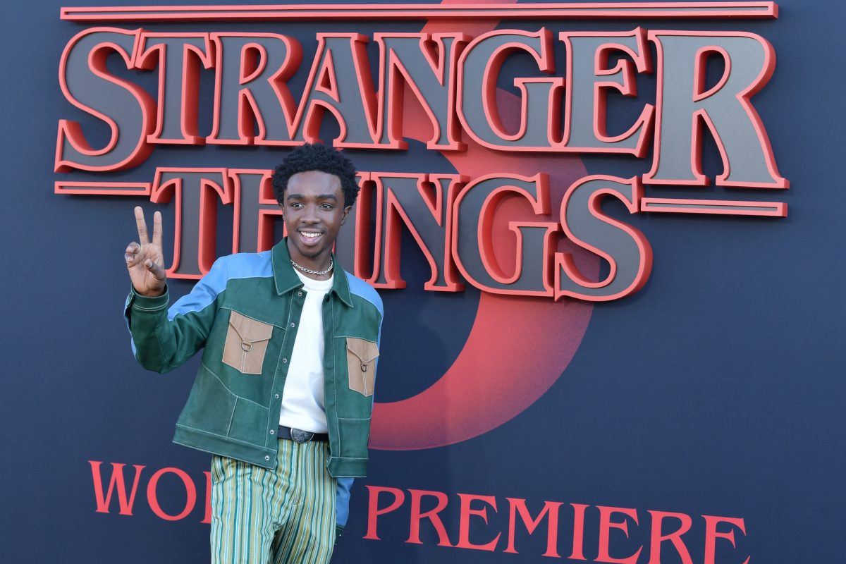 Stranger Things Season 4 star Caleb McLaughlin holds up a peace sign in front of a wall with the show's title on it. He's wearing a green jacket with brown pockets on the front and blue shoulders.