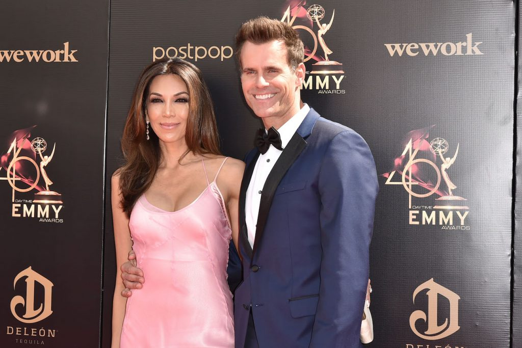 Cameron Mathison standing in front of black background with wife Vanessa Arevalo