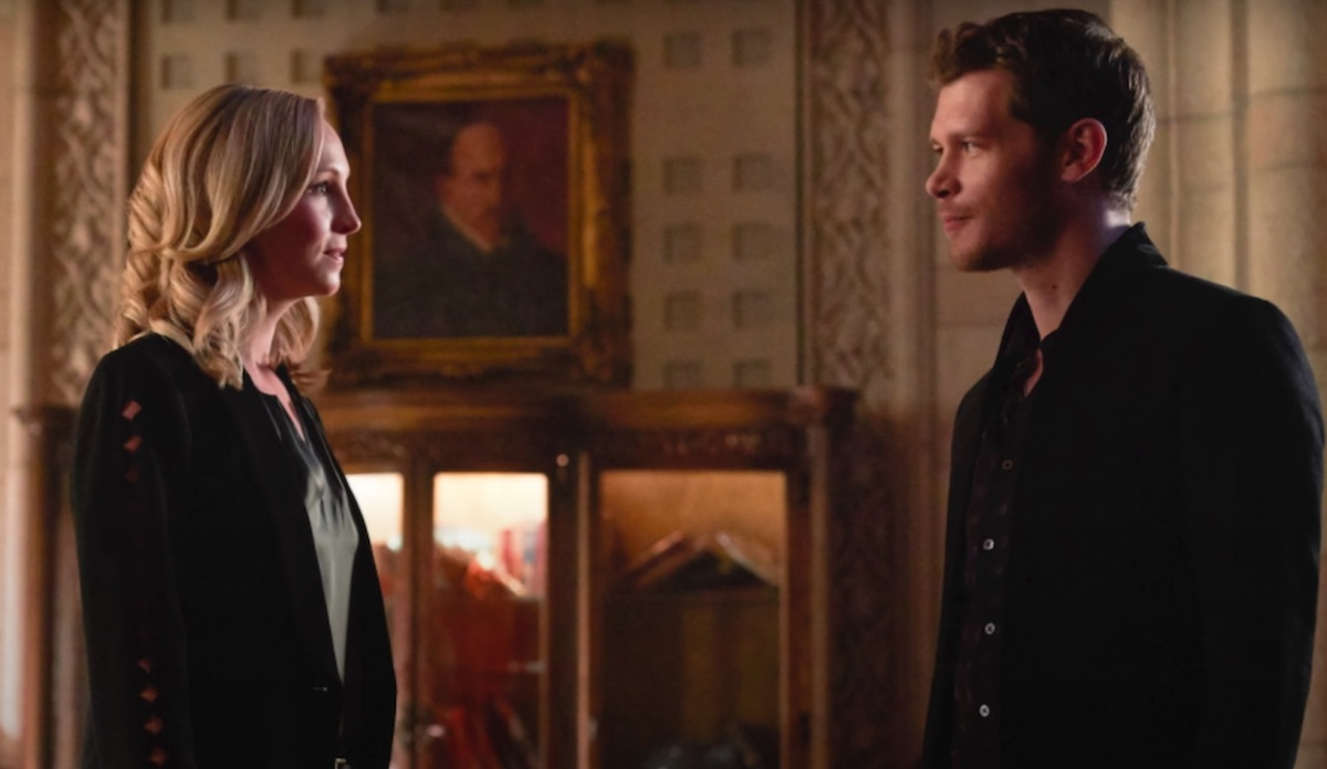 Candice Accola King and Joseph Morgan as Caroline Forbes and Klaus Mikaelson in 'The Originals' Season 5. They stand in a large room with marble walls and art on the walls. They look at each other with smirks on their face. Caroline Forbes and Klaus Mikaelson met in 'The Vampire Diaries' and their will-they-won't-they relationship continued through 'The Originals.'