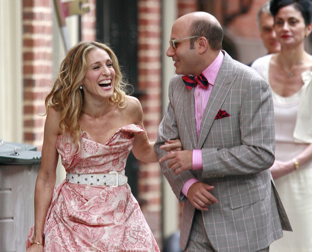 Carrie Bradshaw and Stanford Blatch laugh as they walk down a Manhattan sidewalk for a scene in 'Sex and the City: The Movie'
