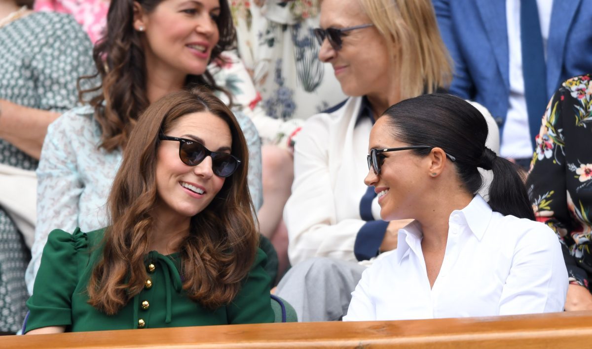 Kate Middleton and Meghan Markle talking at tennis match