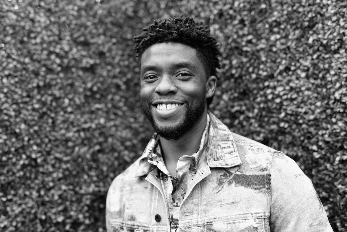 Chadwick Boseman wears a jean jacket smiling as he attends the 2018 MTV Movie And TV Awards at Barker Hangar on June 16, 2018 in Santa Monica, California.