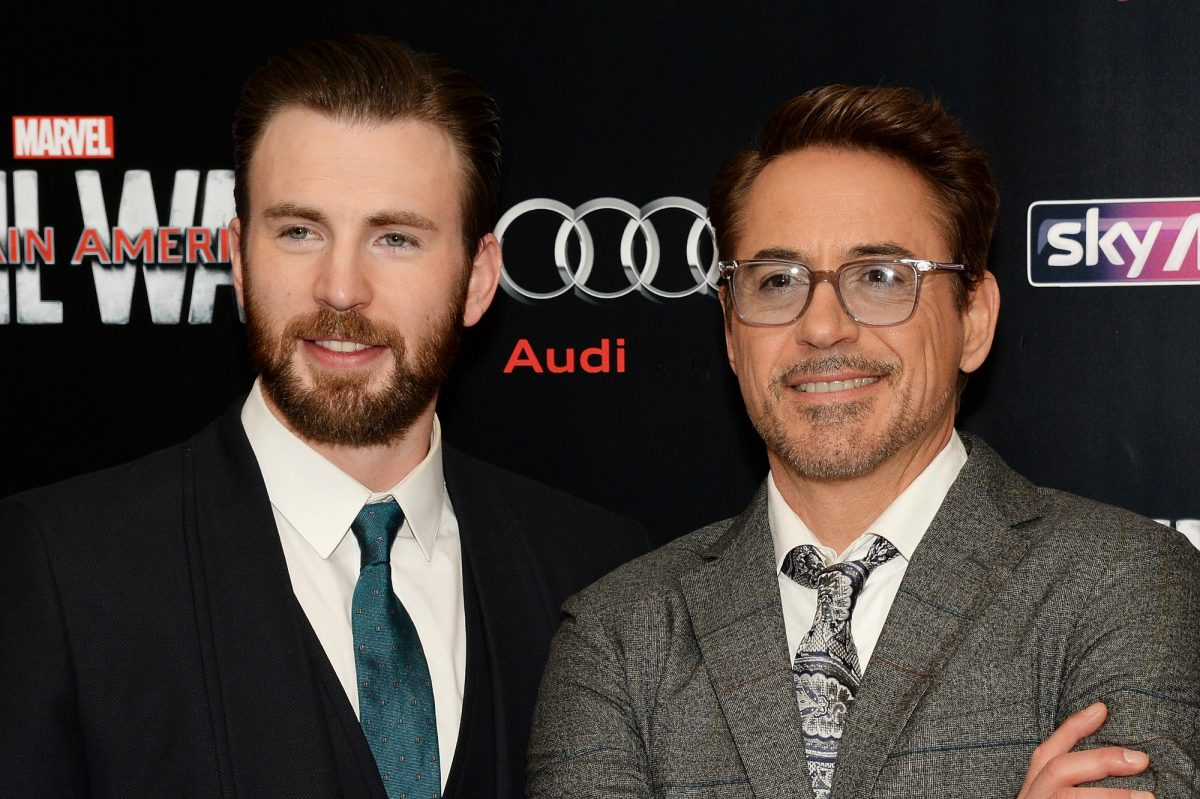 Chris Evans stands next to Robert Downey Jr. at the premiere for 'Captain America: Civil War.' Evans wears a black suit, white shirt, and blue tie. Downey wears a grey suit and tie with a white shirt.
