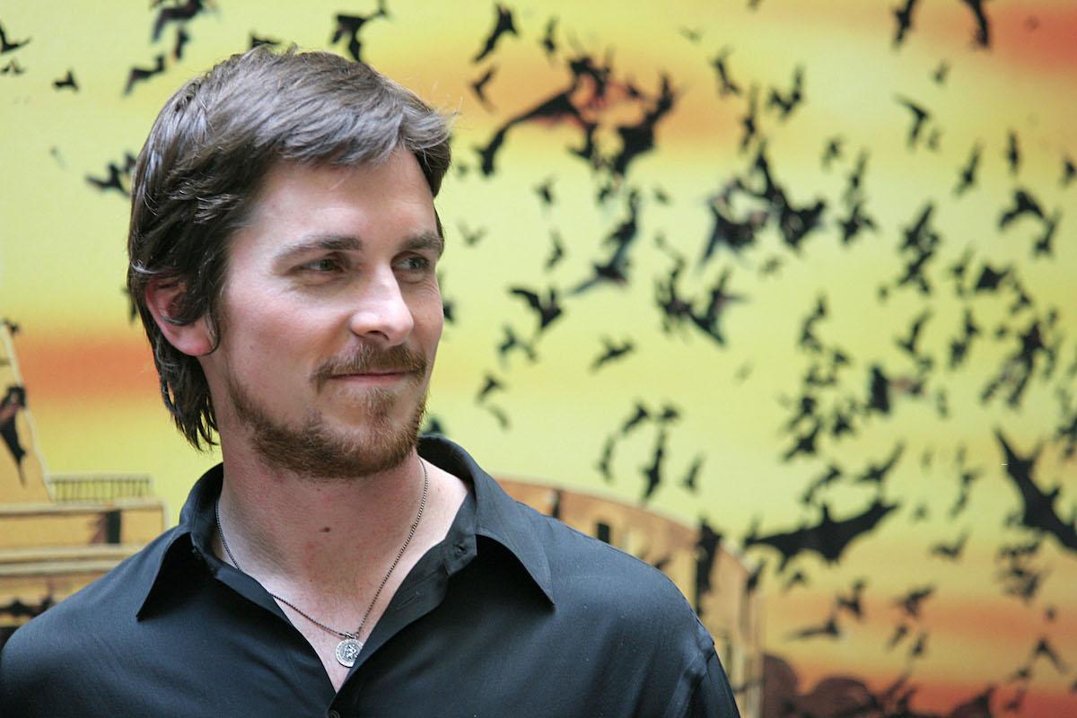 Christian Bale smiles in a dark shirt in front of 'Batman Begins' artwork