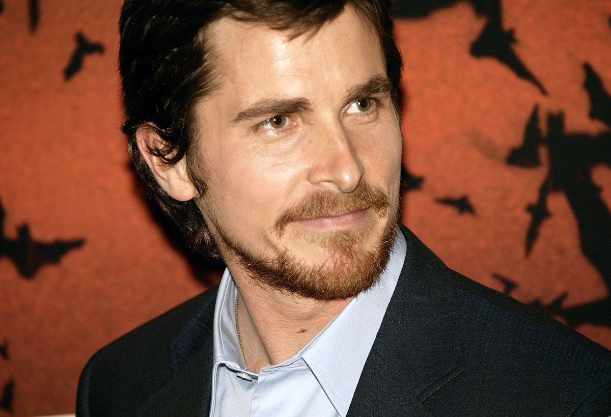 Christian Bale smiles and poses in front of 'Batman Begins' artwork