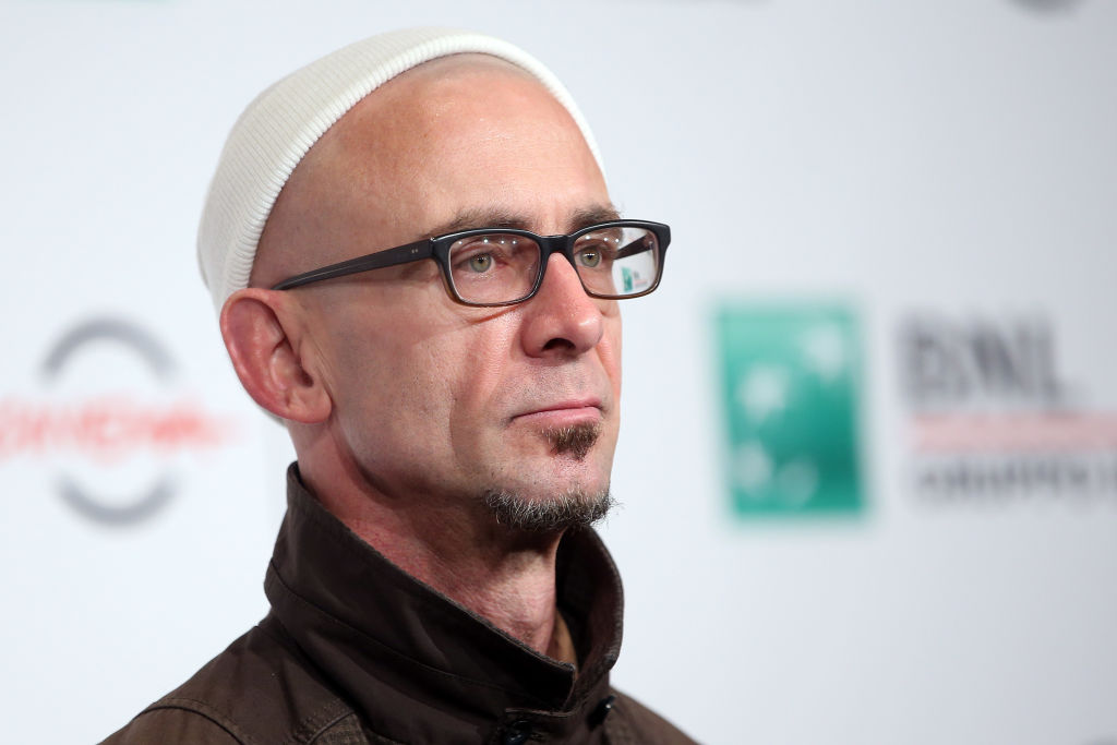 Chuck Palahniuk walks the red carpet in a dark suit and white cap. He wears glasses and looks out to the crowd of photographers with a sullen expression.