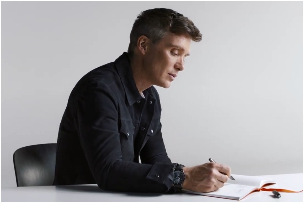 Cillian Murphy sits at a desk and writes in a notebook.