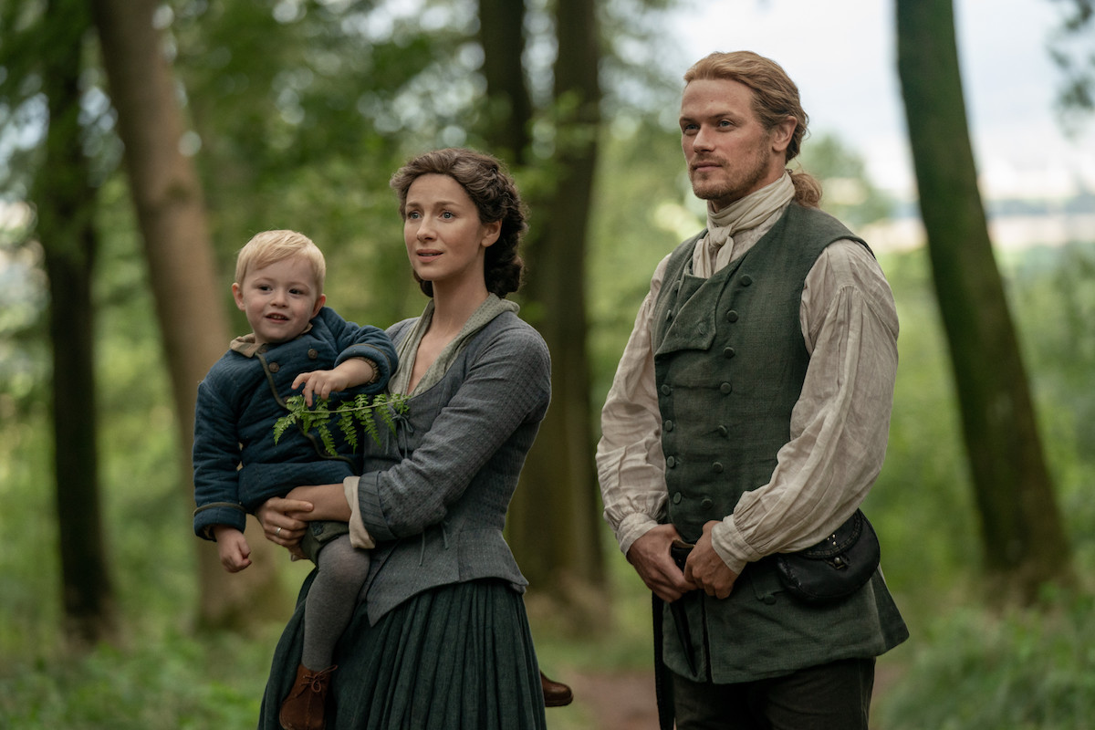 Claire holding baby and standing next to Jamie in 'Outlander' Season 5. The Frasers' lives will be complicated by 'Outlander's Tom Christie and his family in 'Outlander' Season 6. And the trouble will seriously impact Jamie and Claire.