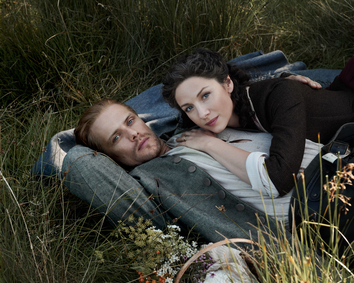 Claire and Jamie from 'Outlander' lying in the grass. In 'Outlander' Season 6, Jamie and Claire's relationship and life on Fraser's Ridge will be challenged by Tom Christie and his family.