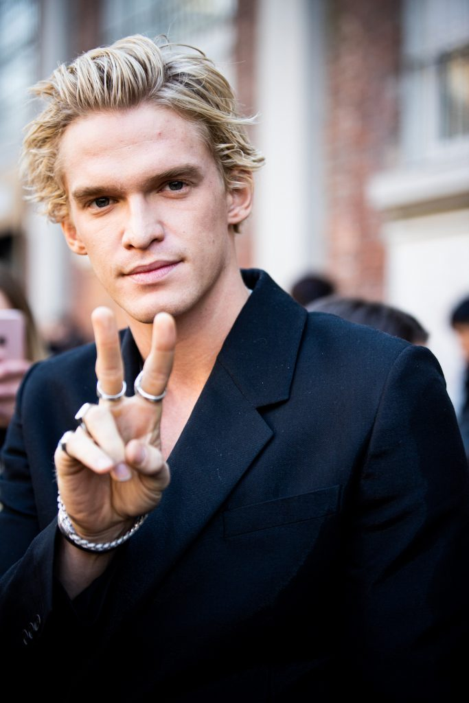 Cody Simpson in a black jacket smiles and flashes a peace sign at the camera.