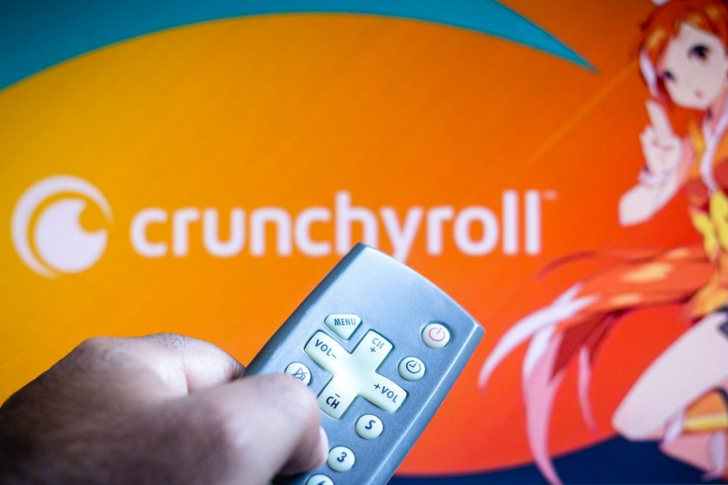 A Crunchyroll logo banner for the anime streaming site with a discount holding a remote in front of it