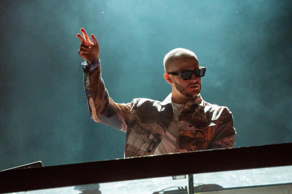 DJ Snake performing on a smoky stage