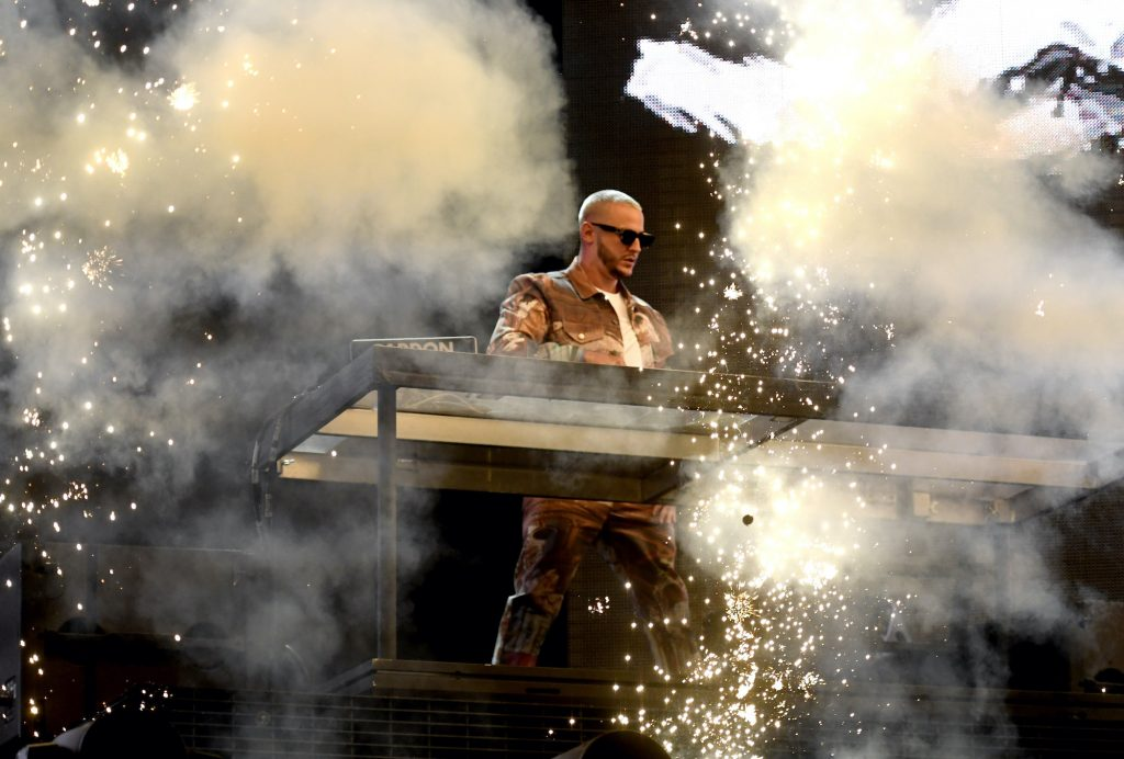 DJ Snake performing on stage with smoke and firework effects in foreground