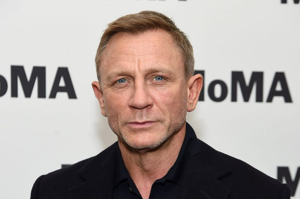 Daniel Craig is dressed in a black button up shirt with a suit jacket in front of a white background with black text.