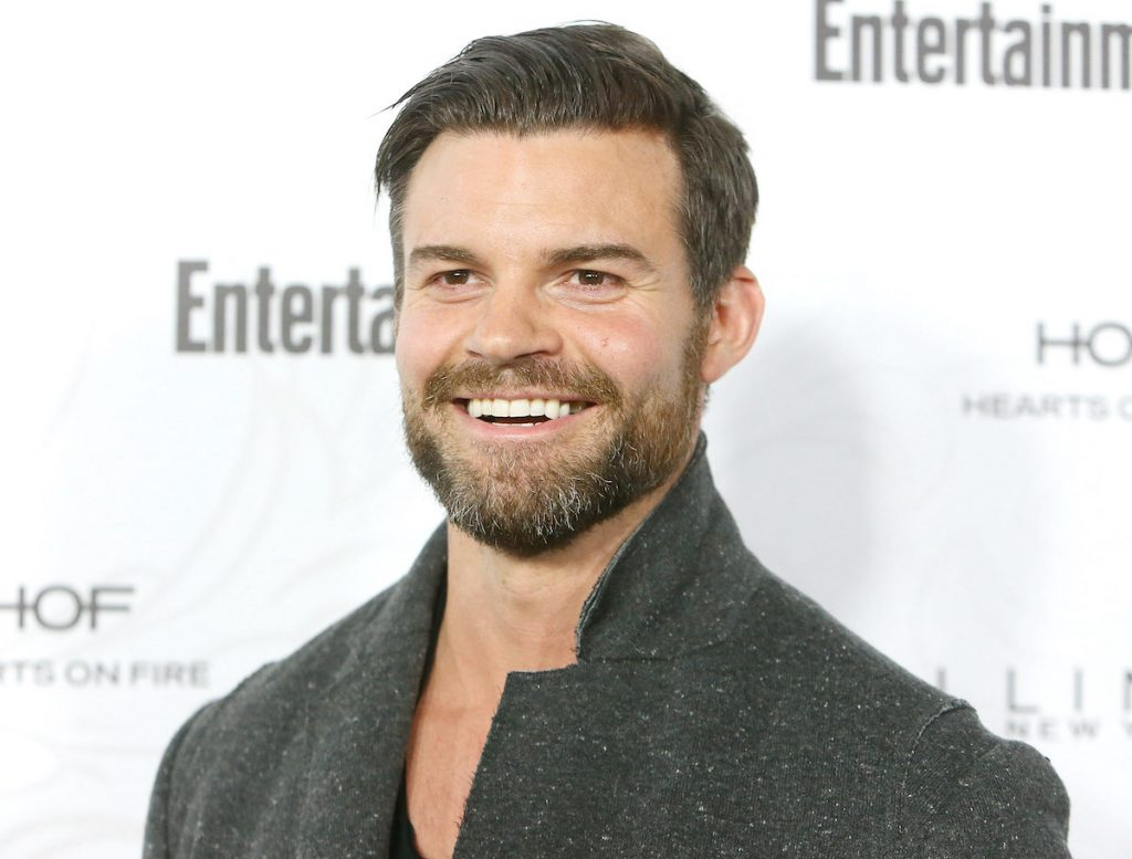 Daniel Gillies smiles on the red carpet wearing a grey jacket
