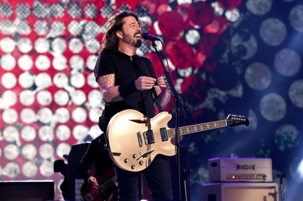 Dave Grohl from the Foo Fighters on stage playing a guitar in a pair of black pants and a black T-shirt in front of a background with red, white, and blue circles.