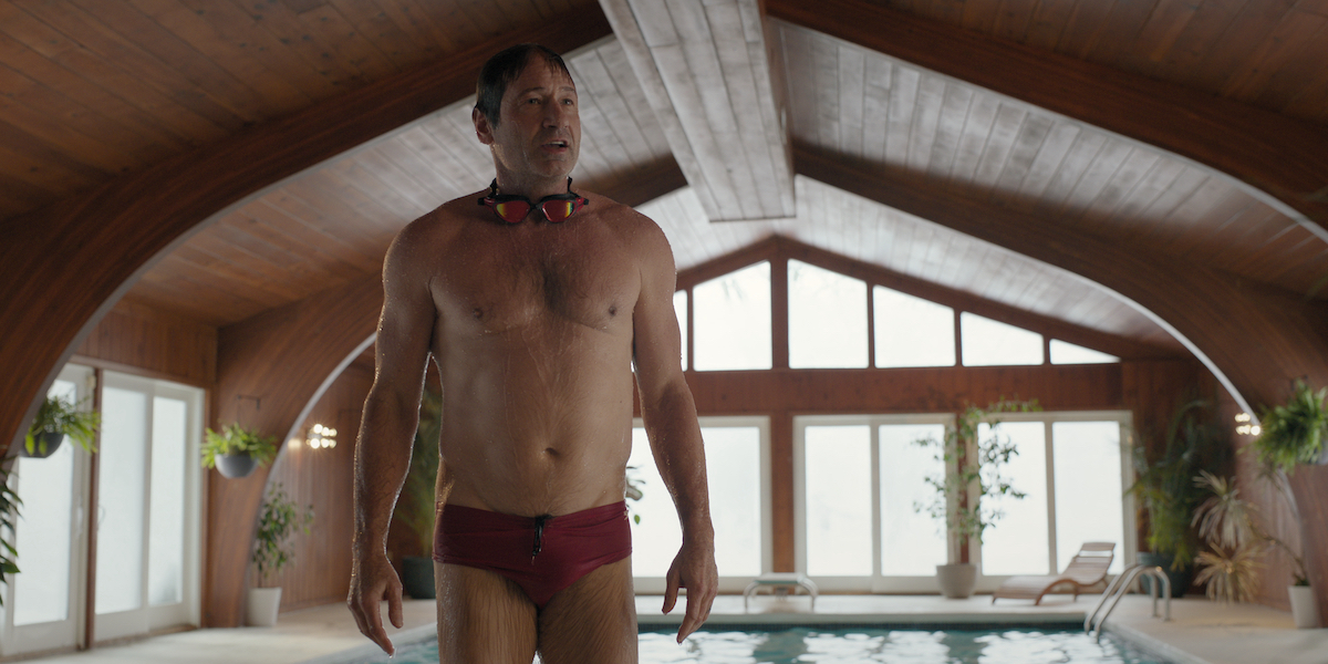 David Duchovny stands next to a pool wearing a Speedo in 'The Chair' Season 1