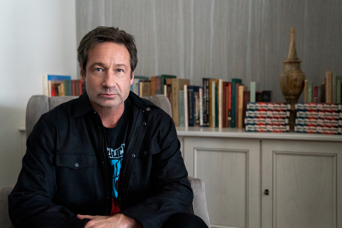David Duchovny sits in a chair with books behind him in 'The Chair'