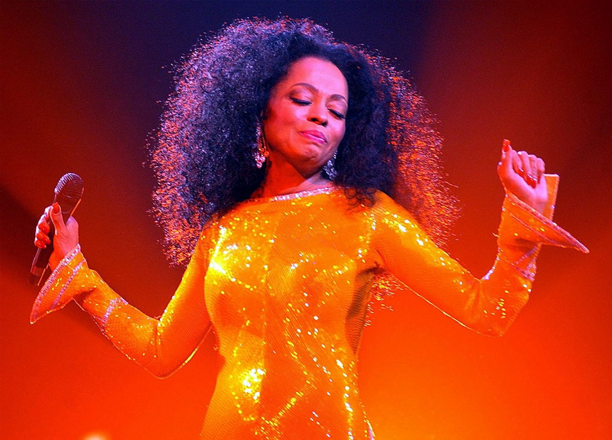 Diana Ross performing onstage in an orange sequined gown.
