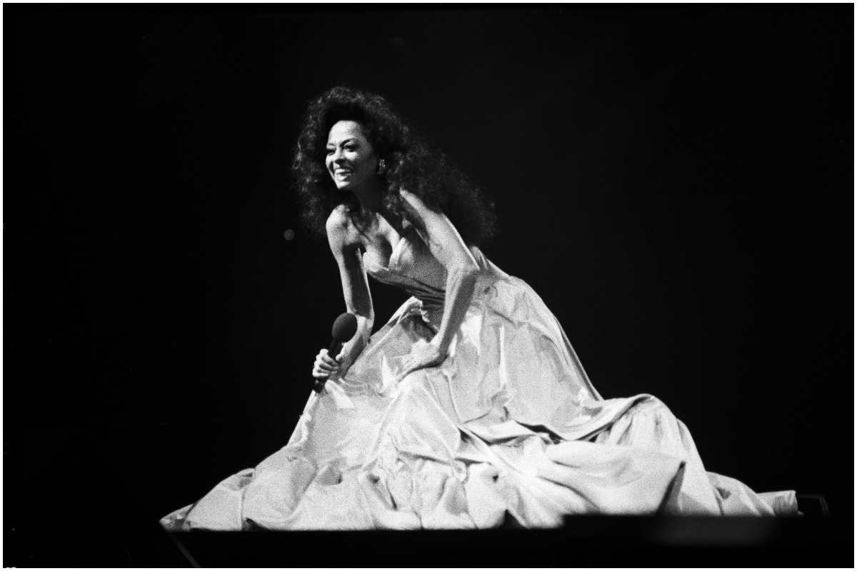 Diana Ross kneeling down and singing in a black and white photo.