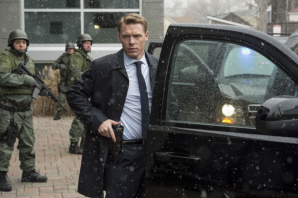 Diego Klattenhoff as Donald Ressler stands with other officers with guns drawn outside.