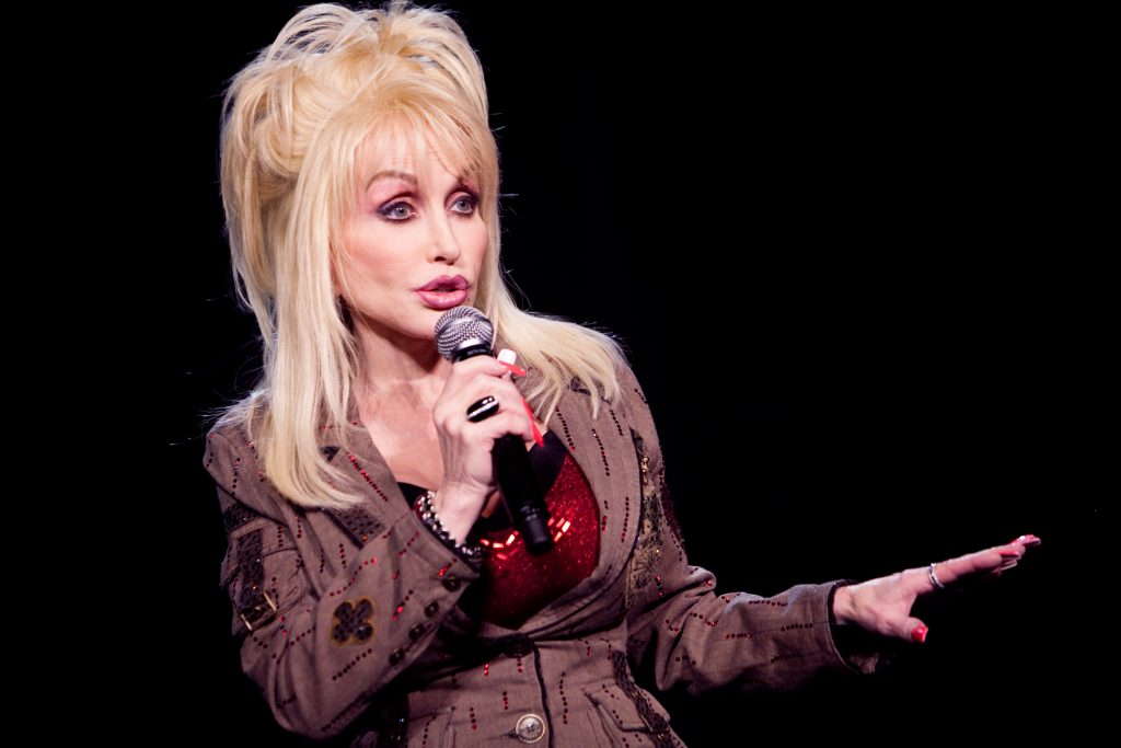Dolly Parton talking into a microphone on stage.